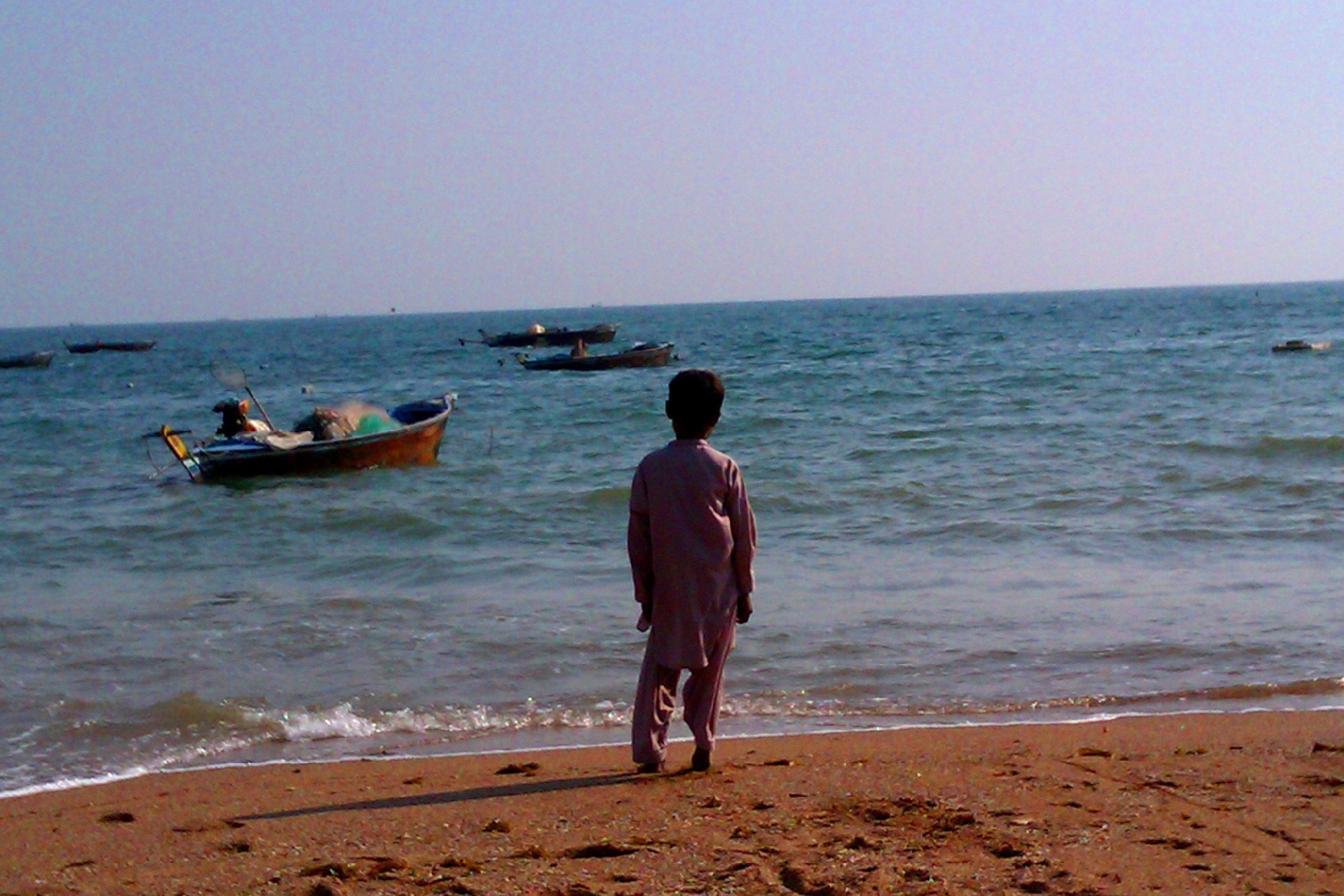 Fisherboy looks to the distant boats. Photograph by Aown Shahzad, Karachi, Pakistan.